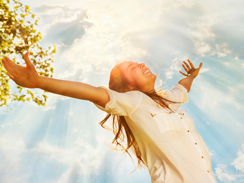 Young woman raising her arms and enjoys sunny day