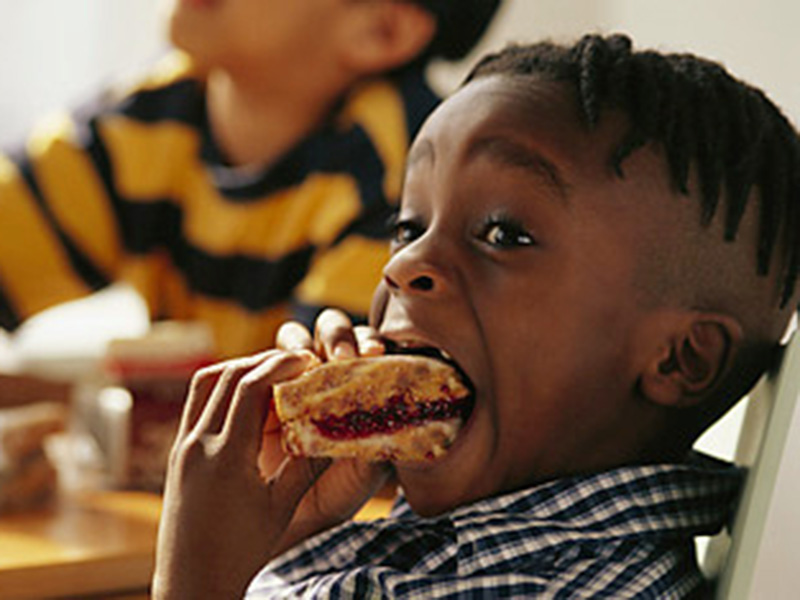 ca. 2002 — Boy Biting into Sandwich — Image by ©LWA-Dann Tardif/CORBIS
